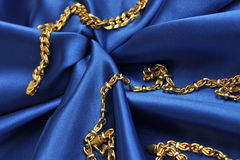 Gold over blue satin. Gold chain over blue satin background Stock Photos