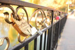 Gold pad lock symbol of love on the bridge. Closed gold padlock with names on russian letters as a symbol of love on the bridge in autumn Stock Photography