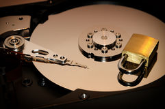 Gold padlock on the opened HDD disk drive surface. Data protection or security concept. Stock Image