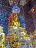 Gold pained Buddha statues in the temple with mural painting. Royalty Free Stock Photo