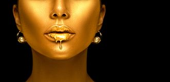 Gold paint drips from the lips, golden liquid drops on beautiful model girl`s mouth, creative abstract makeup. Beauty woman face isolated on black background royalty free stock images
