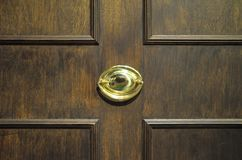 Gold painted door knocker. A photo taken on a gold painted door knocker on a brown wooden door Stock Images
