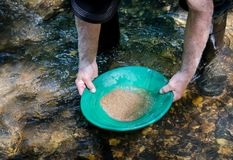Gold pan filled with mineral rich material. Prospecting for gold and gemstones. Fun and adventure enjoying outdoor recreational activity stock images