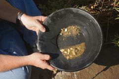 Gold panning, hoping to strike it rich. By finding the mother lode or at least a nugget or two Royalty Free Stock Photography