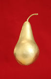 Gold pear on red background Stock Images