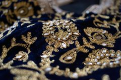 Gold and pearl embroidery on blue velvet. Handcrafted gold and pearl embroidery on blue velvet. Details of indian clothing Stock Photos