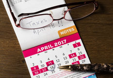 Gold pen laying on calendar for tax day Royalty Free Stock Image