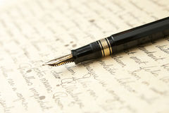 Gold Pen with Letter and Writing. Gold Pen with hand Written Letter in Cursive and Ink Spots Royalty Free Stock Photography