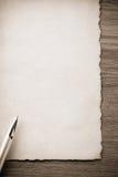 Gold pen on parchment Stock Images