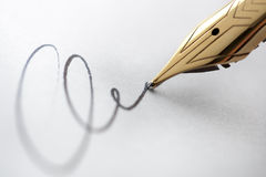 Gold pen with signature. Extreme close up of fountain pen and signature. Selective focus with critical sharpness on tip of pen nib Royalty Free Stock Images