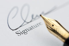 Gold pen with signature. And document in background. Focus on tip of fountain pen nib Royalty Free Stock Photos