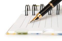 Gold pen writing on notebook Stock Photos