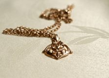 Gold pendant. On a chain lies in the fabric. Pendant is decorated with beautiful patterns Stock Photography