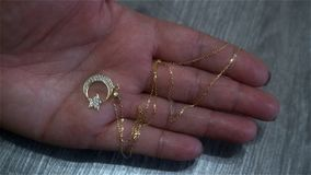Gold pendant in the form of a symbol of Turkey in a female hand.  Royalty Free Stock Image
