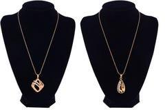 Gold pendant necklace on black velvet mannequine isolated on white background royalty free stock photo