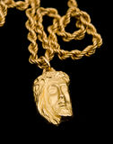 Gold pendant in shape the face of Christ. In isolation on a black background Royalty Free Stock Photo