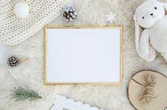 Gold Photo frame mock up with space for text, art work,lettering, pine cone fir branch,rope,rabbit toy on fur background. Flat lay, top view. Cosy, soft stock photography