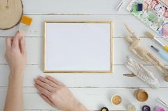 Gold photo frame mock up with woman artist hands. Space for text, art work, lettering. Flat lay, top view. Cosy, soft. Minimal. Fashionable composition stock photography