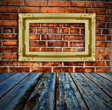 Gold picture frame on brick wall and wood floor Royalty Free Stock Photo