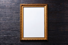 Gold picture frame on Burned wooden background Stock Photography