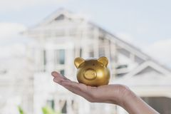 Gold piggy bank on hand women with house construction background. Gold piggy bank on hand women with house construction background Stock Photo