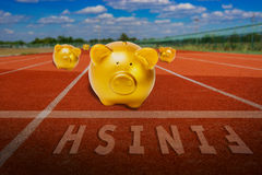 Gold piggy bank runing to finish line. Conceptual idea Royalty Free Stock Photography