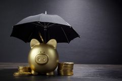 Gold Piggy bank with umbrella concept for finance insurance, protection, safe investment or banking