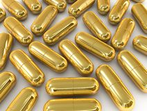 Gold pill capsule. Isolated on white background Royalty Free Stock Photography