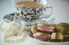 Luxurious gold French macarons and chocolates on a porcelain plate stock photos