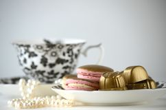 Luxurious gold French macarons and chocolates on a porcelain plate. Gold and pink French macarons, chocolates with a cup of tea, pearls Royalty Free Stock Image