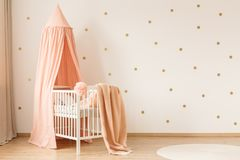 Gold and pink kid`s bedroom. Pink blanket on white crib against wallpaper with gold dots in kid`s bedroom interior stock photography