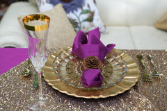 Gold Place setting with a pine cone napkin ring. At a wedding reception royalty free stock images