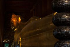 Gold plated body and toes of reclining Buddha statue stock image