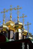 Gold-plated domes with crosses of wooden Russian Orthodox Christian Church of St. Nicholas in Ganina Yama Monastery. Royalty Free Stock Images