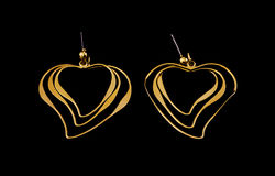 Gold-plated earrings on a black background. Gold-plated earrings in the form of a heart on a black background Royalty Free Stock Photography