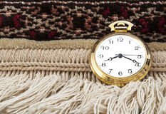 Gold pocket watch. Elegant Gold pocket watch over a carpet Stock Photos