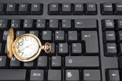 Gold pocket watch and keyboard. Stock Photos