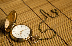 Gold pocket watch on bamboo rugs. Close-up Stock Images