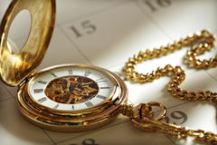 Gold pocket watch and calendar stock photography