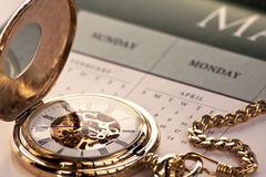 Gold pocket watch and calendar. Close up of a gold pocket watch resting on a calendar royalty free stock images