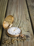 Gold pocket watch and chain against  aged wood Royalty Free Stock Images