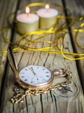 Gold pocket watch and chain against  aged wood Stock Photo