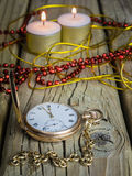Gold pocket watch and chain with decorations and candles against Stock Image