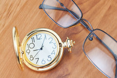 Gold pocket watch and glasses. Stock Photo