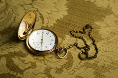 Gold pocket watch on gold cloth Royalty Free Stock Photos