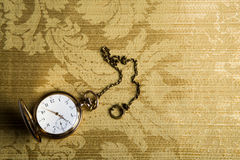 Gold pocket watch on gold cloth Stock Photography