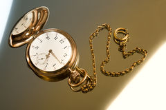 Gold pocket watch on gold glass background. Close-up Royalty Free Stock Image