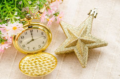 Gold pocket watch and gold star christmas with flower. Royalty Free Stock Image