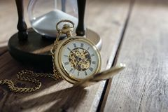 Gold pocket watch and hourglass. Vintage pocket watch and hour glass or sand timer, symbols of time with copy space Stock Photo