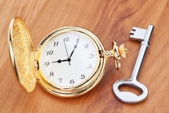 Gold pocket watch and key. Royalty Free Stock Photos
